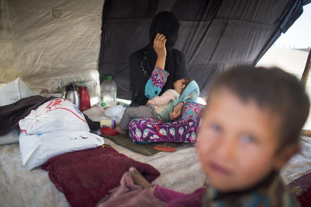 KUNDUZ, AFGHANISTAN- JUNE 20: A woman named Jamillah holds her baby inside a tent in a barren field in Kunduz city. She, like the four other families in tents, fled her village in Chardara district after her house was caught in the crossfire of the conflict. (Majid Saeedi for The Washington Post)